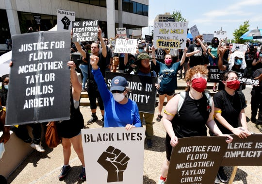 People hold protest signs during the march against police brutality Saturday afternoon, June 6, 2020.