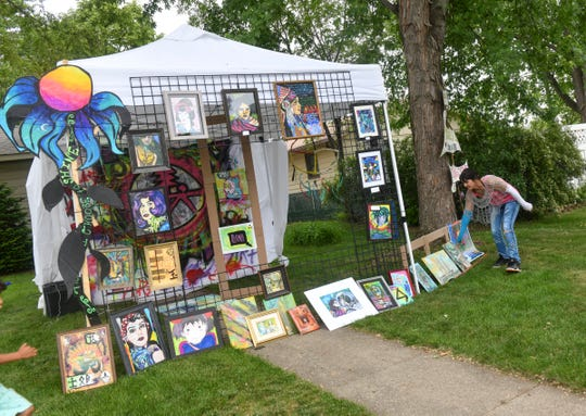 Kelli Henry adjusts pieces of art on display near her home as part of the Drive By Art Show Saturday, June 6, 2020, in St. Cloud.