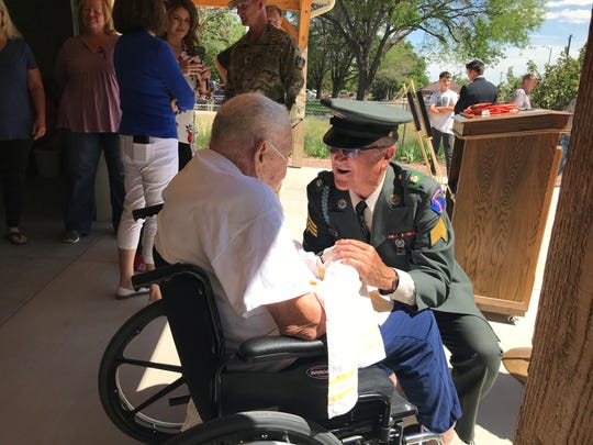 Roddy Roper, left, speaks with Ferron Holt following the presentation of his two bronze stars for acts of valor during World War II. Roper, who had a career in education, was Holt's principal.