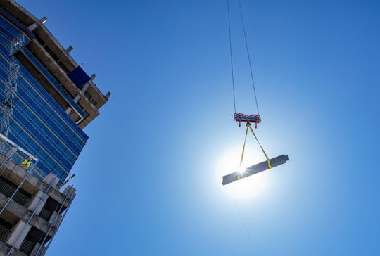 The final steel beam is hoisted to the top of the 19-story WestStar Tower at Hunt Plaza during a May 21 topping-off ceremony.