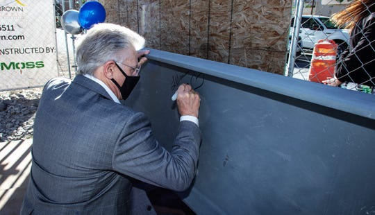 Rick Francis, Westar Bank CEO, signs the final metal beam for the top of the WestStar Tower at Hunt Plaza during a May 21 topping-off ceremony for the Downtown office building.