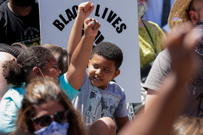A pair of children raise their fists during a protest on Saturday, June 6, 2020, at Wausau City Hall in Wausau, Wis. Hundreds of protesters gathered and marched in response to George Floyd's death in police custody on May 25 in Minneapolis.Tork Mason/USA TODAY NETWORK-Wisconsin
