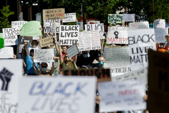 Protesters hold up signs before a march on Saturday, June 6, 2020, at  in Wausau, Wis. Hundreds of protesters gathered and marched in response to George Floyd's death in police custody on May 25 in Minneapolis.