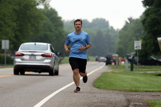 Pastor Justin Williams, of Coburn United Methodist Church, runs along Airport Road near Zanesville recently. Williams is running past the homes of his church members and and praying for each of them.