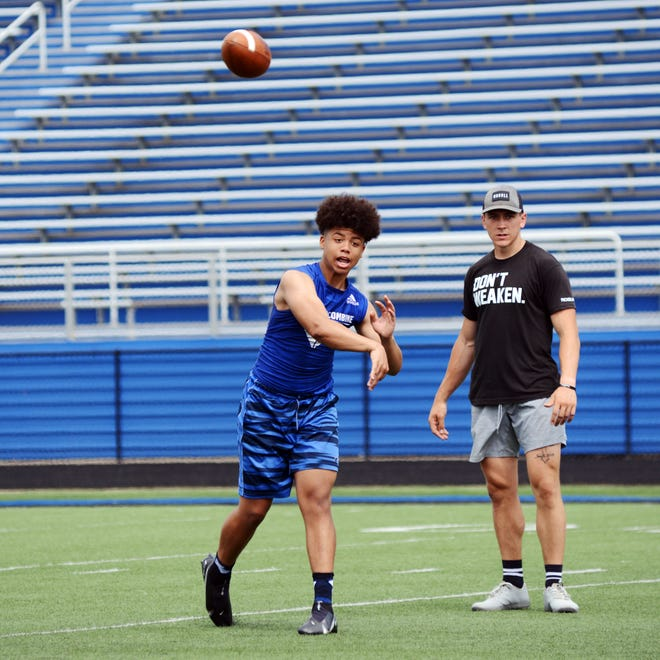 Zamesville quarterback Jeremiah Miller throws to a teammate during receiving drills on Saturday at John D. Sulsberger Memorial Stadium. Also picured is assistant coach Thomas Wibbeler.