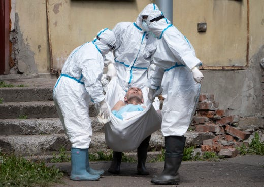 Medical workers wearing protective gear to protect against coronavirus infection, carry a patient at an infectious diseases hospital where patients with coronavirus are treated in St.Petersburg, Russia, June 3, 2020.
