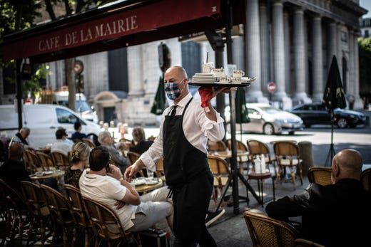 A masked waiter works at the terrace of the Cafe de la Mairie on the Place Saint-Sulpice in Paris on June 2, 2020, as cafes and restaurants reopen in France, while the country eases lockdown measures taken to curb the spread of the COVID-19 (the novel coronavirus).