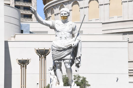 The Caesar statue at the entrance to Caesars Palace sports a gold mask as the hotel casinos reopen after a 2 1/2-month shutdown.