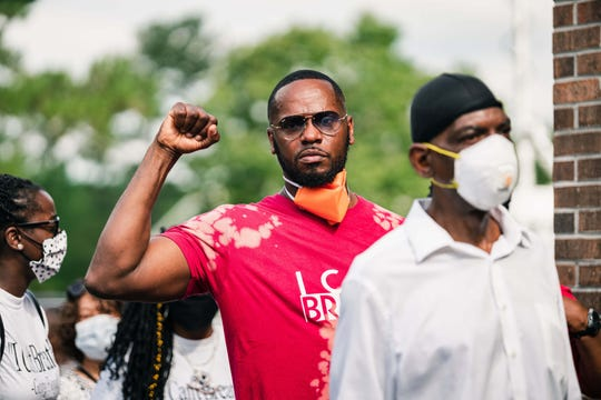 A man holds up a fist before a memorial held for George Floyd.