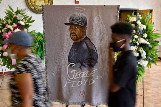 People walk by a mural for George Floyd as they pay their respects during a memorial June 6 in North Carolina.