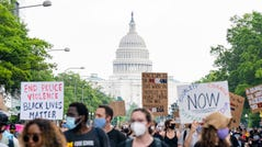 The United States Capitol building is seen as demonstrators display and march along Constitution Avenue in Washington, DC.