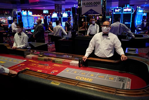 Dealers in masks wait for customers before the reopening of the D Las Vegas hotel and casino, June 3, 2020, in Las Vegas. Casinos were allowed to reopen on Thursday after temporary closures as a precaution against the coronavirus.