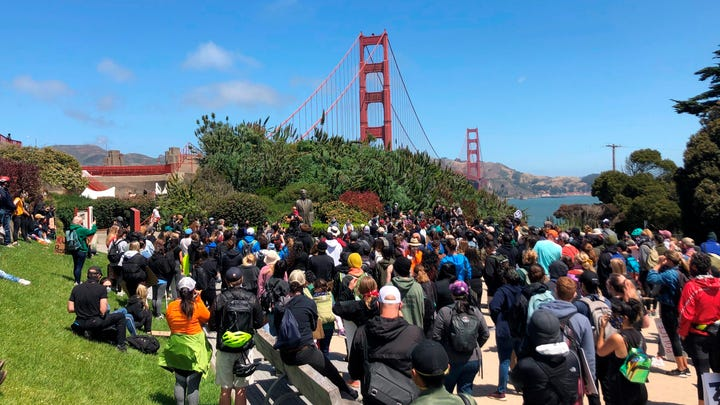 Dozens of people gather by the Golden Gate Bridge Welcome Center in San Francisco Saturday, June 6, 2020.