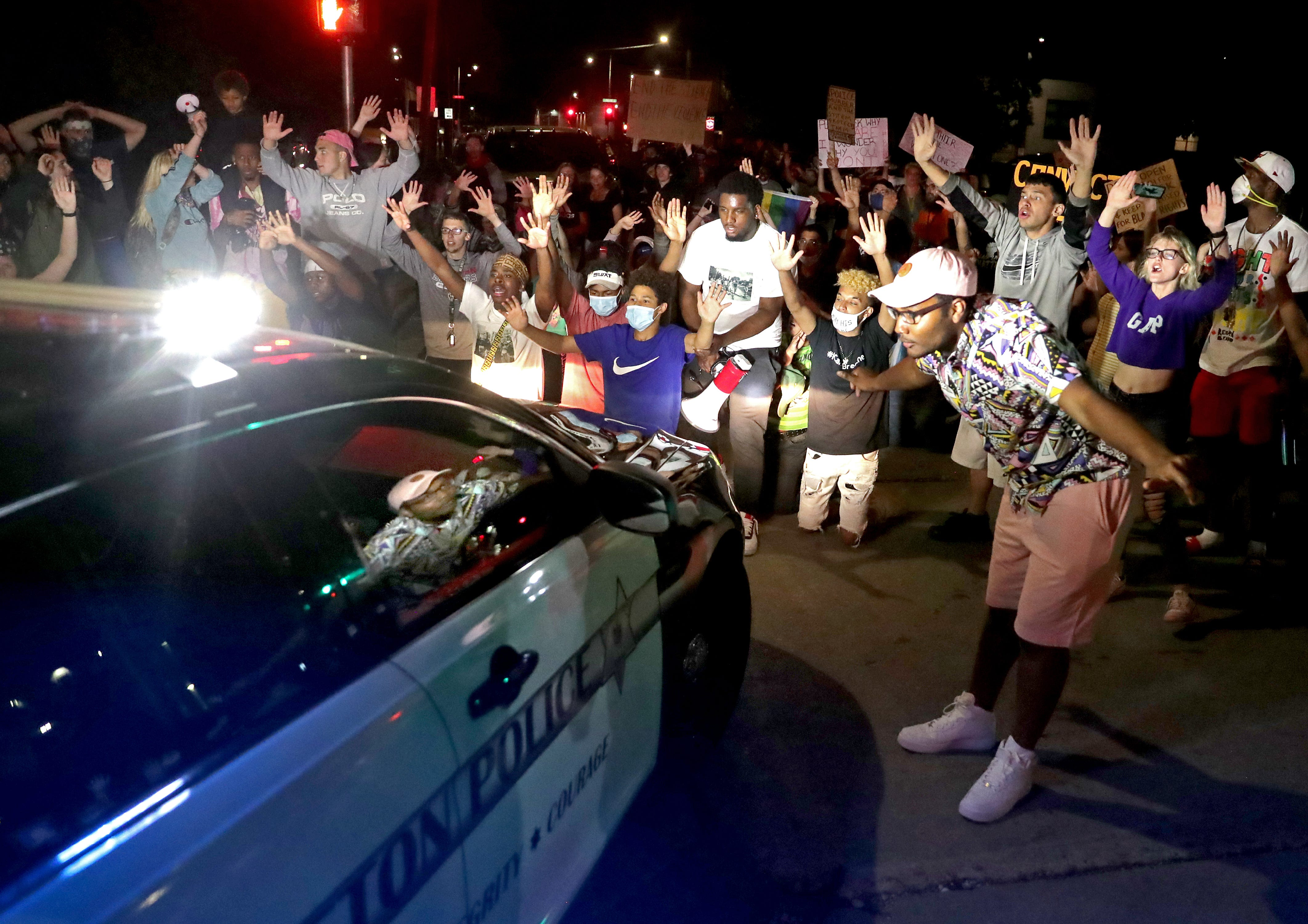 Protesters surround an Appleton police car in front of the police station during a Black Lives Matter protest on Saturday, June 6, 2020, in Appleton, Wis.