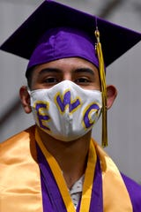 "Kaleb Chacon wore a customized mask with EWC written across during the Merkel High School graduation Saturday. He said the letters stand for ""ending world corruption,"" something he and his friends came up with."