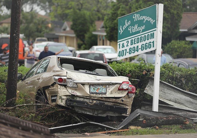 A damaged vehicle and debris sit in front of Lake Margaret Village Apartments Sunday, June 7, 2020, following a tornado that struck late Saturday, in Orlando, Fla.  (Stephen M. Dowell/Orlando Sentinel via AP)
