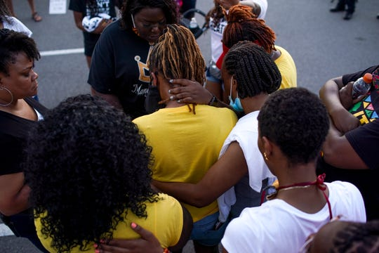 Friends and loved ones gather around, embracing and placing hands on Juanita Charles, center, following an emotional monologue during the Breathe Clarksville rally at Veteran's Plaza in Clarksville, Tenn., on Saturday, June 6, 2020.