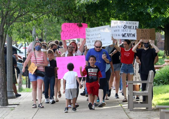 A long line of protestors, reaching more than halfway around the court square, march in condemnation of social injustice on Saturday in Coshocton.
