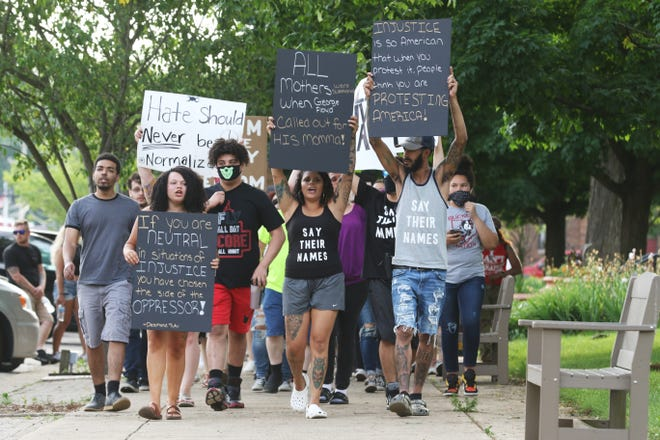 Kiara Strupe, left, and Monique and Allen Weatherwax lead a march around the court square in downtown Coshocton on June 6. Around 350 gathered to demonstrate against social injustice, racism and police brutality.