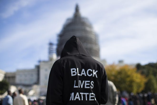 A man wearing a Black LIves Matter hoodie stands near the U.S. Capitol building. America should improve education inequality.