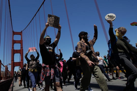 People march as traffic is stopped on the Golden Gate Bridge in San Francisco, Saturday at a protest over the Memorial Day death of George Floyd.