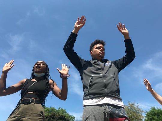 """Kevin Barrett, right, and Desiree Cooper chant """"Hands up, don't shoot,"""" during a protest for police reform Sunday in Green Bay."""