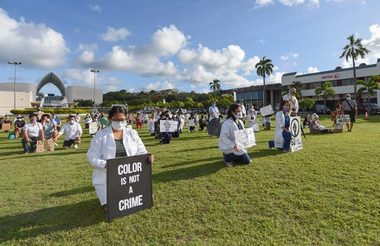 Supporters of the White Coats for Black Lives movement hold a silent protest while either kneeling, sitting, or standing for 8 minutes and 46 seconds, symbolizing the amount of time that George Floyd was pinned down, at Skinner Plaza in Hagåtña, June 7, 2020.