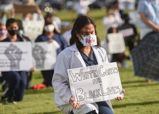 Dr. Mariana Cook-Huynh, a family medicine physician and White Coats for Black Lives organizer, leads a silent protest at Skinner Plaza in Hagåtña, June 7, 2020.