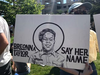"""A protester holds a sign reading, """"Breonna Taylor, say her name,"""" at a protest in downtown Indianapolis on Saturday, June 6, 2020."""