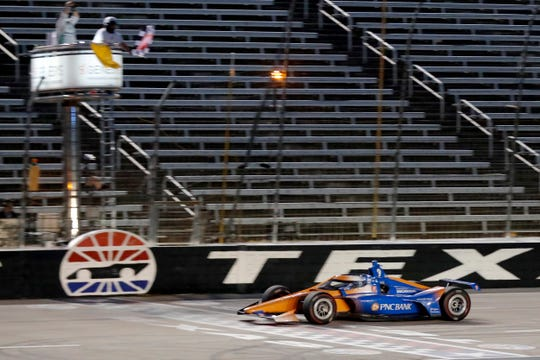 Scott Dixon earns the checkered flag as he crosses the finish line to win an IndyCar auto race at Texas Motor Speedway in Fort Worth, Texas, Saturday, June 6, 2020.