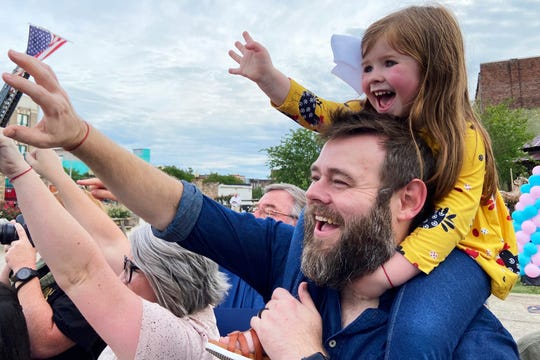 """Todd Tilghman and his daughter, Winnie, wave during a parade in his honor at Dumont Plaza in Meridian, Miss., Thursday, May 28, 2020. Tilghman won the singing competition """"The Voice""""on May 19."""