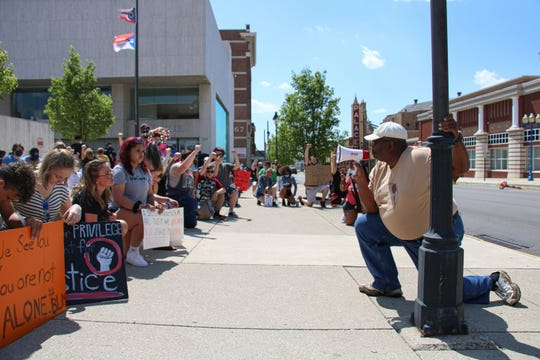 Local radio personality Silky Ray Macklin takes a knee while he speaks to the protesters on Saturday, June 6, 2020, at Marion City Hall.