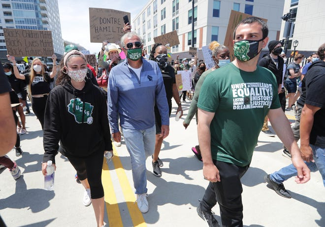 Milwaukee Bucks owner Marc Lasry, center, and his son, Milwaukee Bucks Senior Vice President Alex Lasry, march down East Juneau Avenue in Milwaukee in support of social justice.
