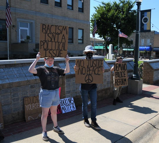 Protesters (from left) Jada Baker, John Wiseman and Callie Parker hold signs Sunday on the Baxter County Courthouse square.