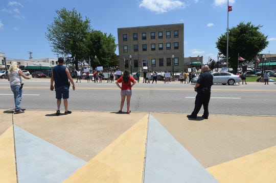 A woman and two men armed with pistols hurl insults back and forth with protesters Sunday on the square in Mountain Home.
