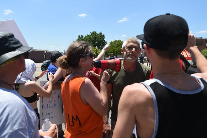 A protester with a bullhorn has an argument with a man in a green shirt who was in disagreement with at least some of the sentiments of the protesters.