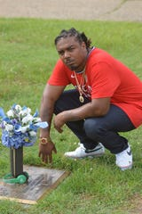 """Chri$ Lowe kneels by the grave of Montgomery rapper Doe B on Saturday, June 6, 2020 at Greenwood Cemetery in Montgomery, Ala., during a video shoot for the YunRo song """"Street Life"""" that Lowe is featured in."""