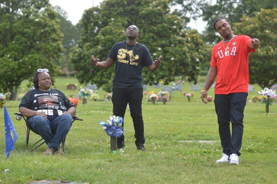 """Doe B's mother Shirley Thomas, YunRo, center, and Chri$ Lowe by the grave of Montgomery rapper Doe B on Saturday, June 6, 2020 at Greenwood Cemetery in Montgomery, Ala., during a video shoot for """"Street Life."""""""