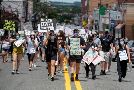 Jasmyne Mena, 23 organizer of a Black Lives Matter march and rally in Rutherford, and her boyfriend Noel Lazo, center, lead the march to demand justice for the murder of George Floyd and other Black Americans up Union Ave. on Sunday, June 7, 2020.