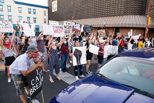 Protesters chant for motorists who are stopped at a red light to honk their horns in support of the Black Lives Matter protest in Hanover's Center Square on Saturday, June 6, 2020. Hundreds of people turned out to peacefully protest the death of George Floyd and other victims of police brutality.