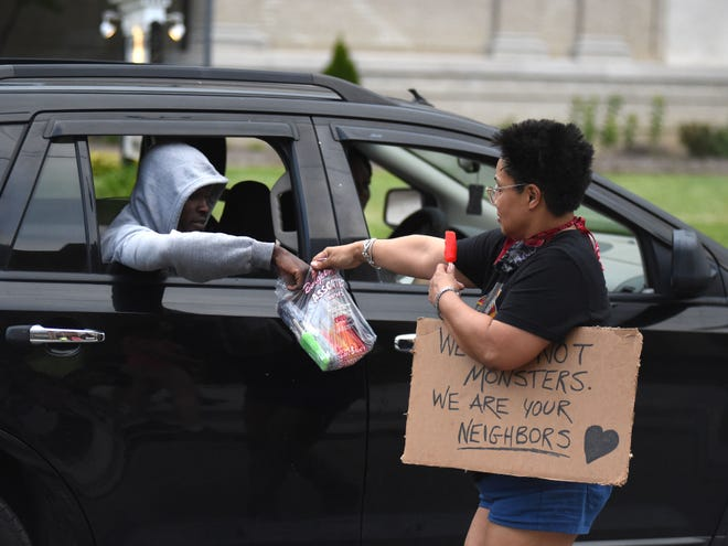 Stacey Strawn hands out a popsicle to a passenger in a care driving down S. Waynes Avenue in Waynesboro Saturday. Strawn was part of a group of protesters who gathered to advocate for racial equality and justice.