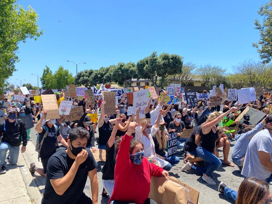 Protesters kneel on Victoria Avenue near the Ventura County Government Center Sunday as a large gathering supporting the Black Lives Matter movement spilled onto the street.