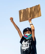 Cuauhtemoc Flores Machado, 8, stands with protesters gathered Saturday, June 6, 2020 to support Back Lives Matter at Mooney Boulevard and Caldwell Avenue.