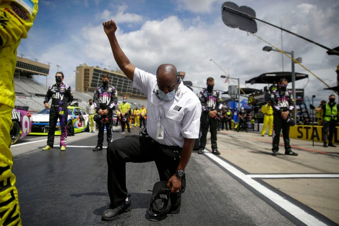A NASCAR official kneels during the national anthem before during the Folds of Honor Quik Trip 500 at Atlanta Motor Speedway.