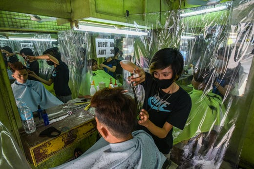 A barber cuts the hair of a customer at a barbershop as it reopened after closing due to the COVID-19 coronavirus in Quezon City, Manila on June 7, 2020.