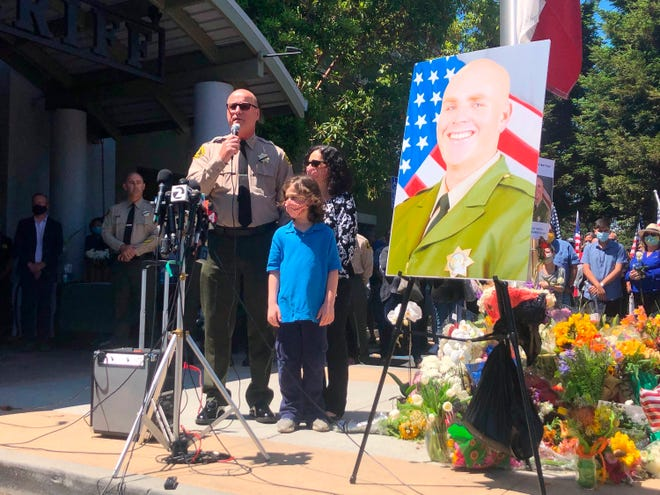 Santa Cruz Sheriff Jim Hart speaks while standing next to a photo of fallen Sgt. Damon Gutzwiller as more than a thousand people gather outside the Santa Cruz County Sheriff-Coroner's Office to pay their respects in Santa Cruz, Calif., Sunday, June 7, 2020.