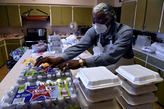 Iziar Lankford adds bottles of water to the meal packages he created June 2 at Bethel United Methodist Church. Lankford has retired from full-time pastor work but still does the occasional funeral or steps in for pastors needing a break.