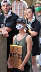 """Jennifer Rogers holds a """"Black Lives Matter"""" sign at Sunday's community rally at Abilene Christian University. Most of those attending the evening event wore masks, at least some of the time."""