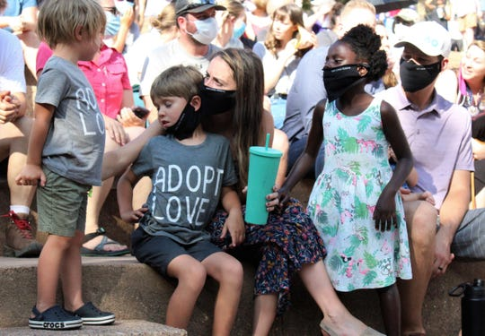 From left, Jones, Judah, mom Elise, Sandrina and Keith Perry, with baby Boaz in his lap, before the start of Sunday's community rally at the amphitheater at Abilene Christian University. Early on, many braved the sun to hear a number of speakers.