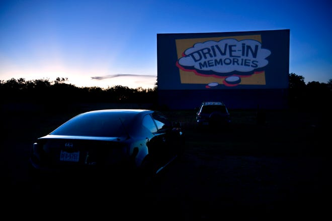 """Advertisements and trivia cards play on a screen at Town & Country Drive-In Theatre before Friday's showing of """"Jurassic Park"""" June 5, 2020."""